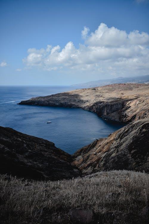 Braune Und Schwarze Felsformation Neben Blauem Meer Unter Blauem Und Weißem Bewölktem Himmel
