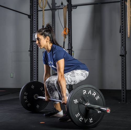 Young Woman in Sports Wear Lifting Barbell