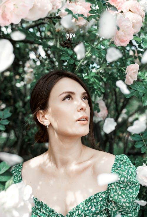Mulher Com Vestido Floral Verde Em Pé Sob Flores Cor De Rosa
