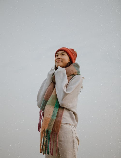 Content ethnic woman in warm clothes on gray background