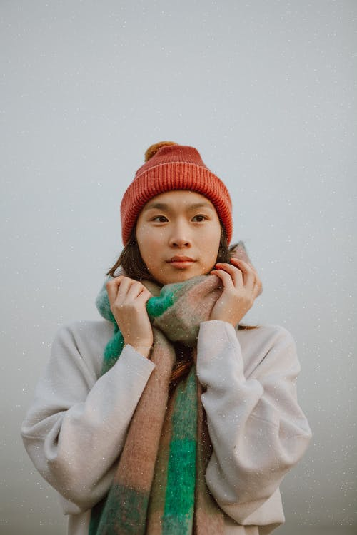 Young contemplative ethnic female with sincere gaze in knitted hat and ornamental scarf looking away