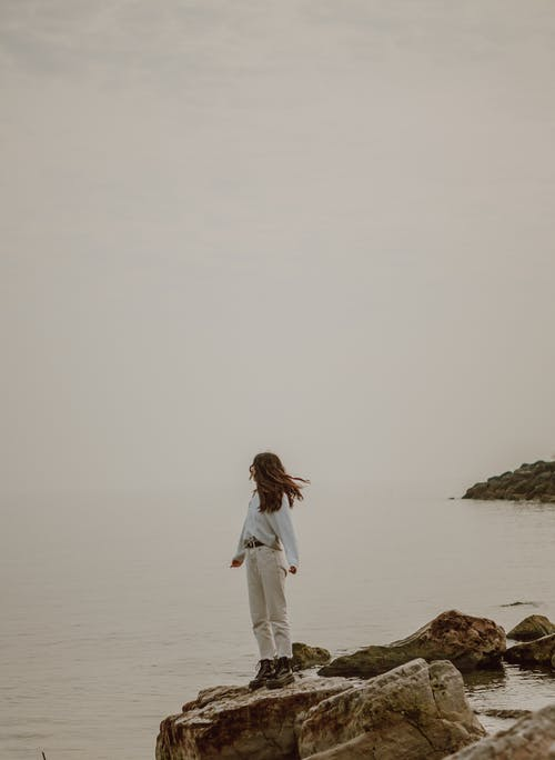 Anonymous tourist admiring sea from stone in misty weather