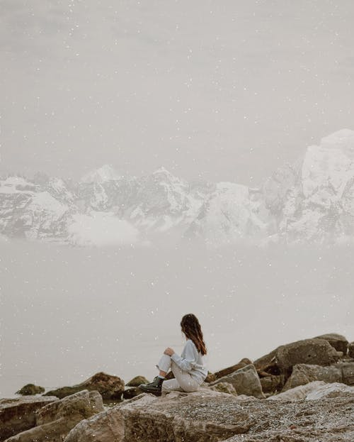 Side view of anonymous female tourist sitting on rough mount against ocean and snowy ridge in foggy weather