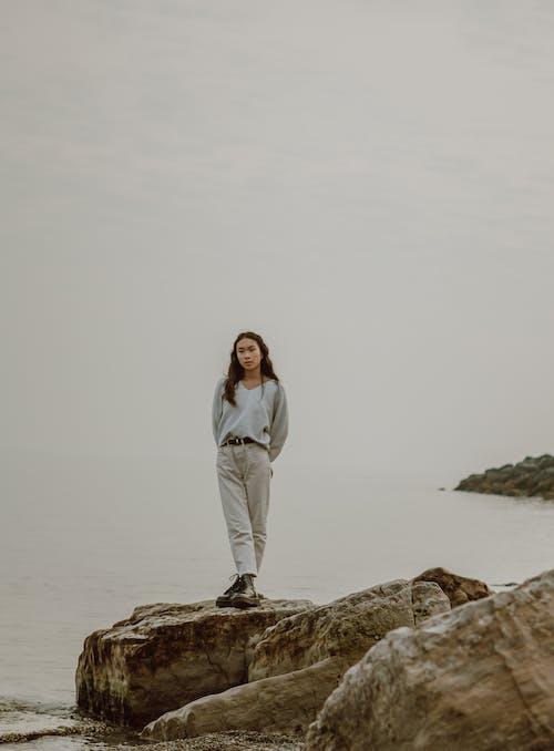Dreamy Asian traveler on boulder against misty sea and sky