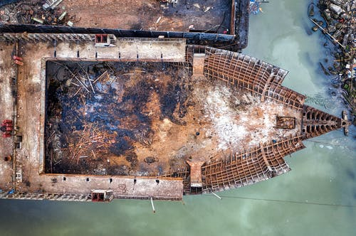 Drone view of old rusty ship floating in polluted water and moored in abandoned dirty port in daylight