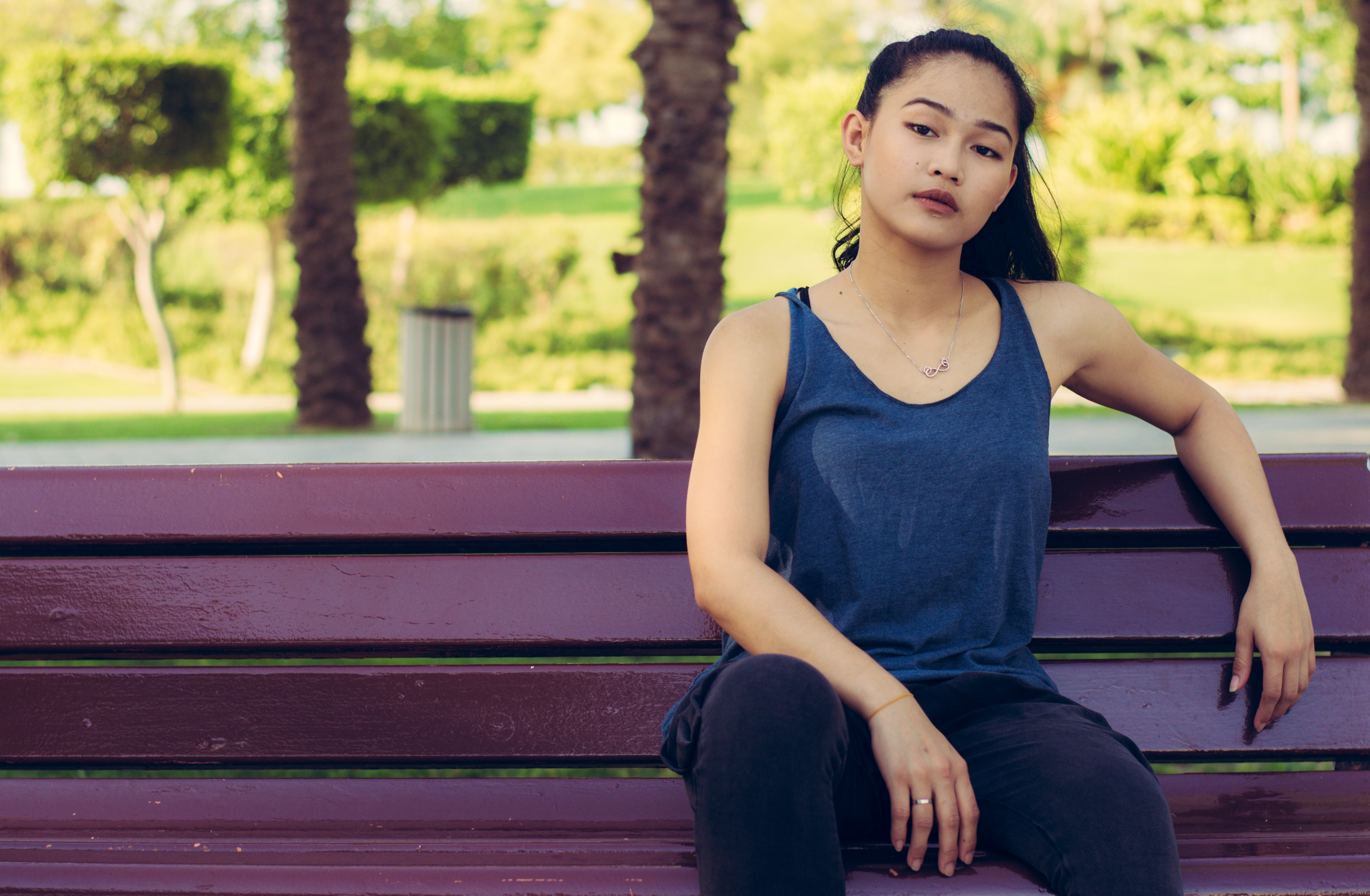 Woman Sitting on Brown Wooden Bench