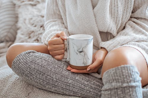 Crop woman with mug of hot drink on bed