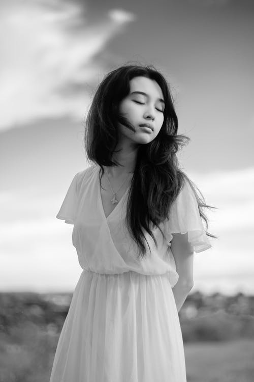 Mindful Asian woman in elegant dress in countryside