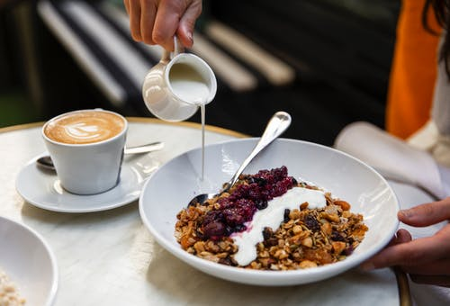 Unrecognizable person having breakfast at table with coffee and muesli