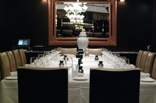 Elegant restaurant with banquet table covered with tablecloth with glasses and napkins near plates and small bottles near chairs and mirror on wall with chandelier reflection near urn for ashes