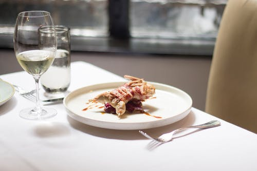 Tablecloth on table with delicious plate with small roasted bird covered in bacon with sauce near glasses with wine and water near forks and knife in light restaurant near chair