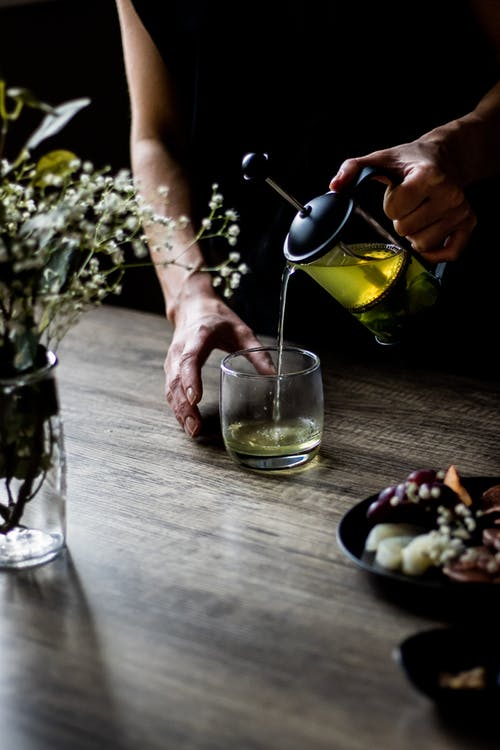 Person Pouring Wine on Clear Drinking Glass