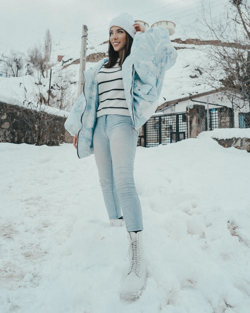 Stylish smiling woman on snow in countryside