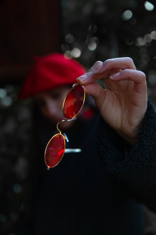 Person Holding Red Framed Sunglasses