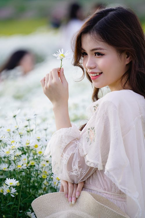 Smiling Asian teenager with blooming chamomile in countryside