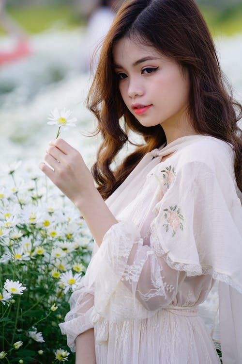 Side view of tender ethnic female teen in elegant wear with blooming flower and makeup looking away in countryside