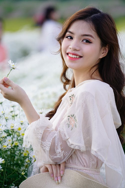 Charming Asian teen with blooming chamomile in countryside