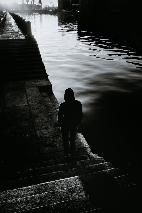 Anonymous person silhouette contemplating water channel in town