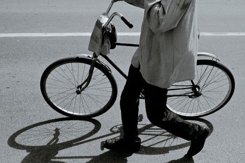 Side view of black and white crop anonymous person in stylish outfit walking on asphalt road with bicycle on sunny day