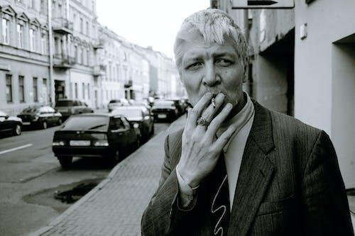 Serious trendy man smoking cigarette on city street