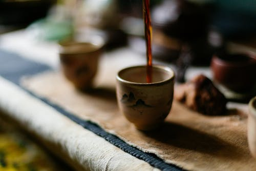 High angle of freshly prepared hot coffee pouring into ceramic cup placed on table in traditional oriental cafe