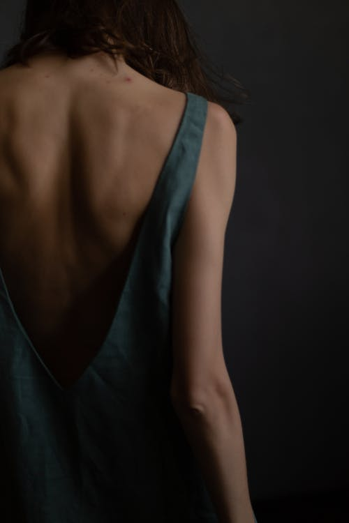 Back view of crop unrecognizable fit female model with dark hair in trendy dress standing against gray background