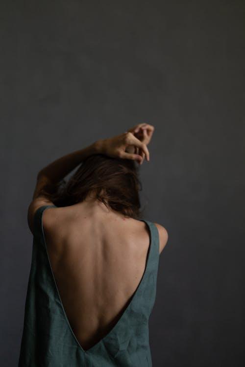 Elegant young woman touching head in gray studio