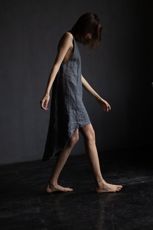 Side view of upset young barefooted female with dark hair in stylish dress walking in dark room and looking down