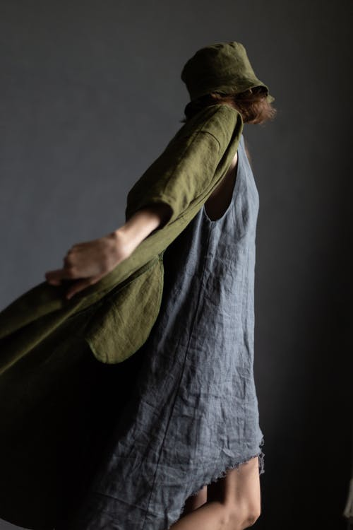 Side view of unrecognizable young trendy female model in fashionable linen dress and coat and hat standing against gray background in studio