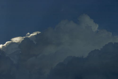 Breathtaking view of big white fluffy clouds floating in blue sky in daytime