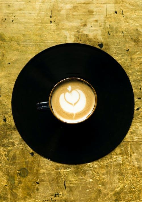 Белая керамическая кружка с кофе на черной круглой тарелке