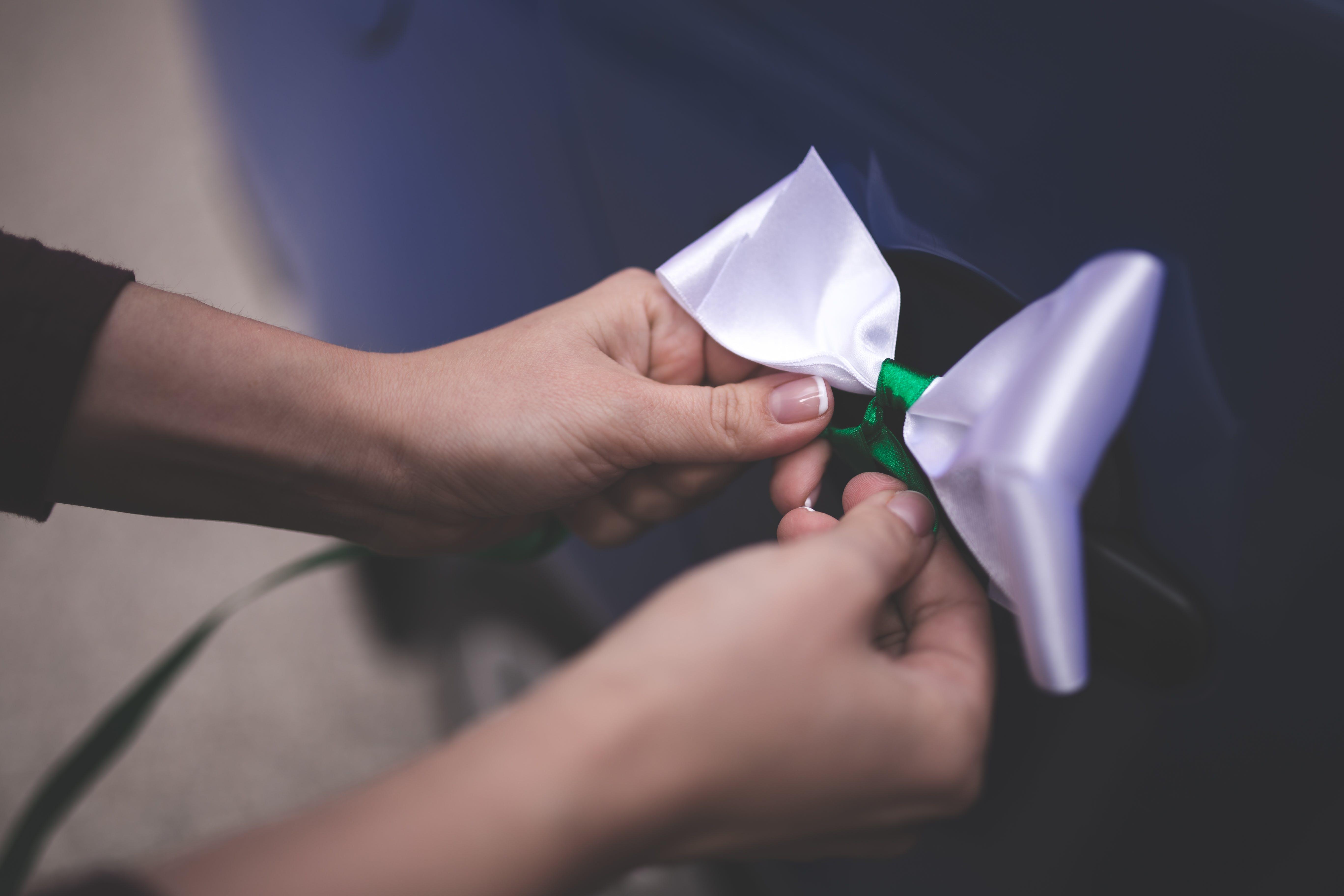 Woman tying a white bow