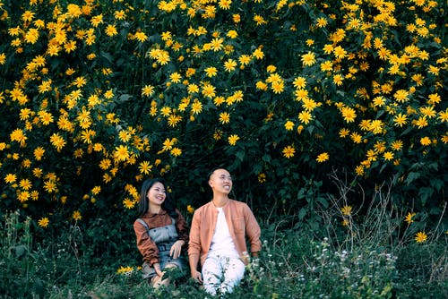 Cheerful Asian couple sitting on grass