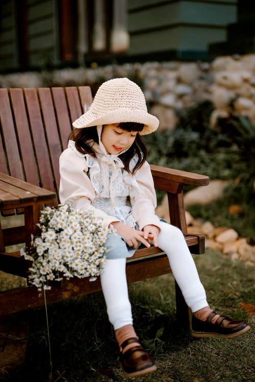 Girl in White and Pink Floral Long Sleeve Shirt Sitting on Brown Wooden Bench