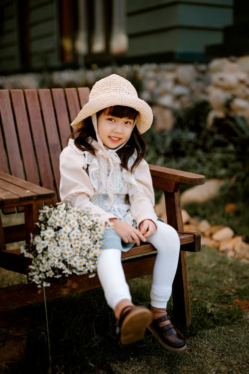 Woman in White Long Sleeve Shirt and White Pants Sitting on Brown Wooden Bench