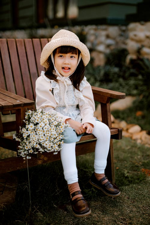Girl in White Long Sleeve Shirt and White Pants Sitting on Brown Wooden Bench