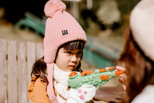 Girl in Pink Knit Cap Holding Green and White Toy Gun