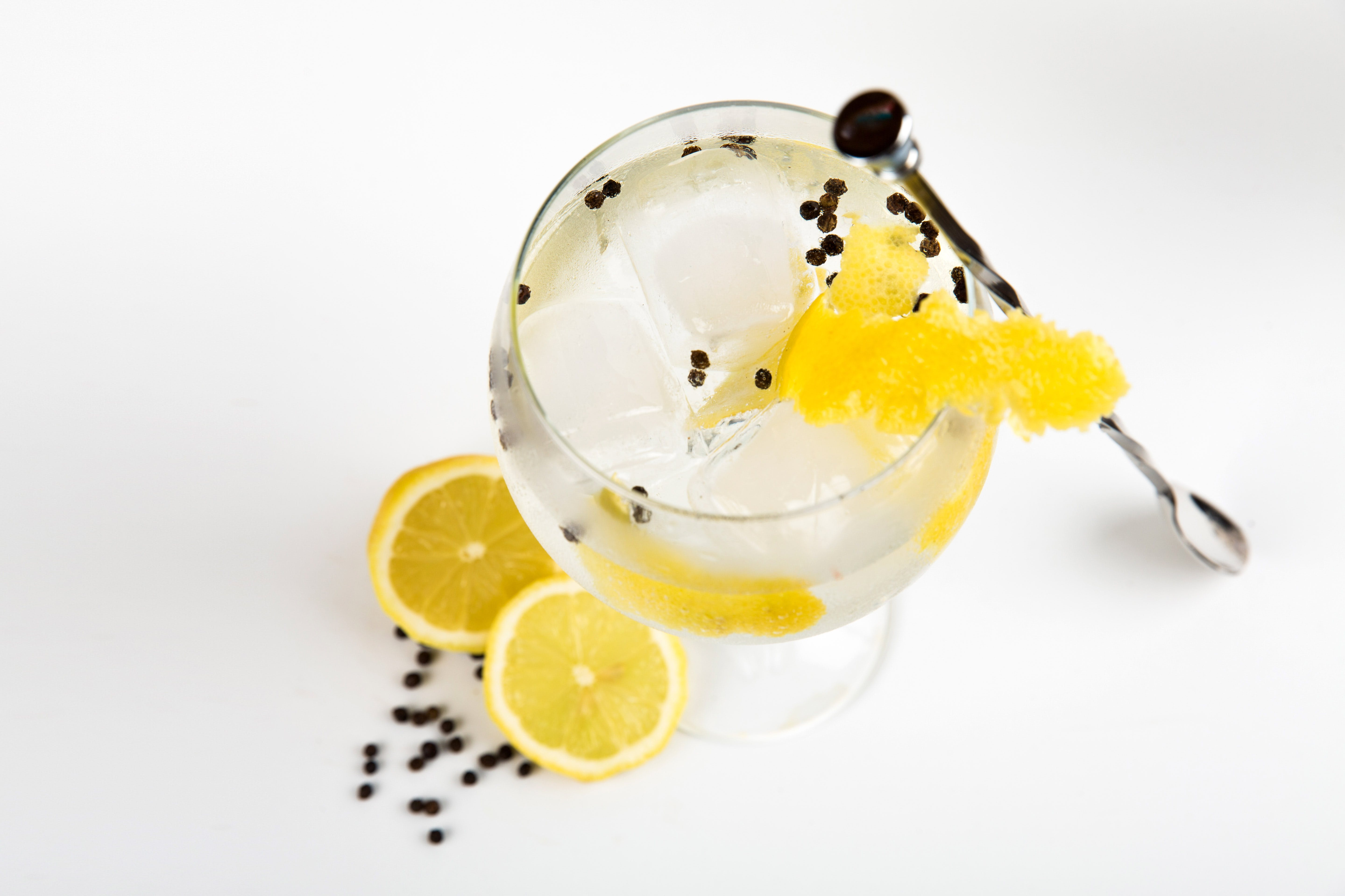 Liquor With Ice Cubes and Slice of Yellow Fruit