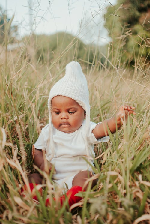 Baby in White Shirt and White Knit Cap Sitting on Brown Grass Field