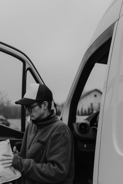 Grayscale Photo of Man in Jacket and Cap in Car