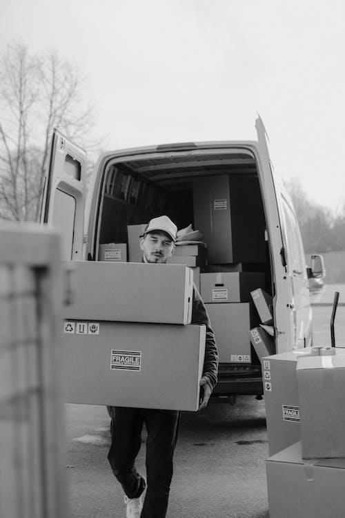 Grayscale Photo of Man in Cardboard Box