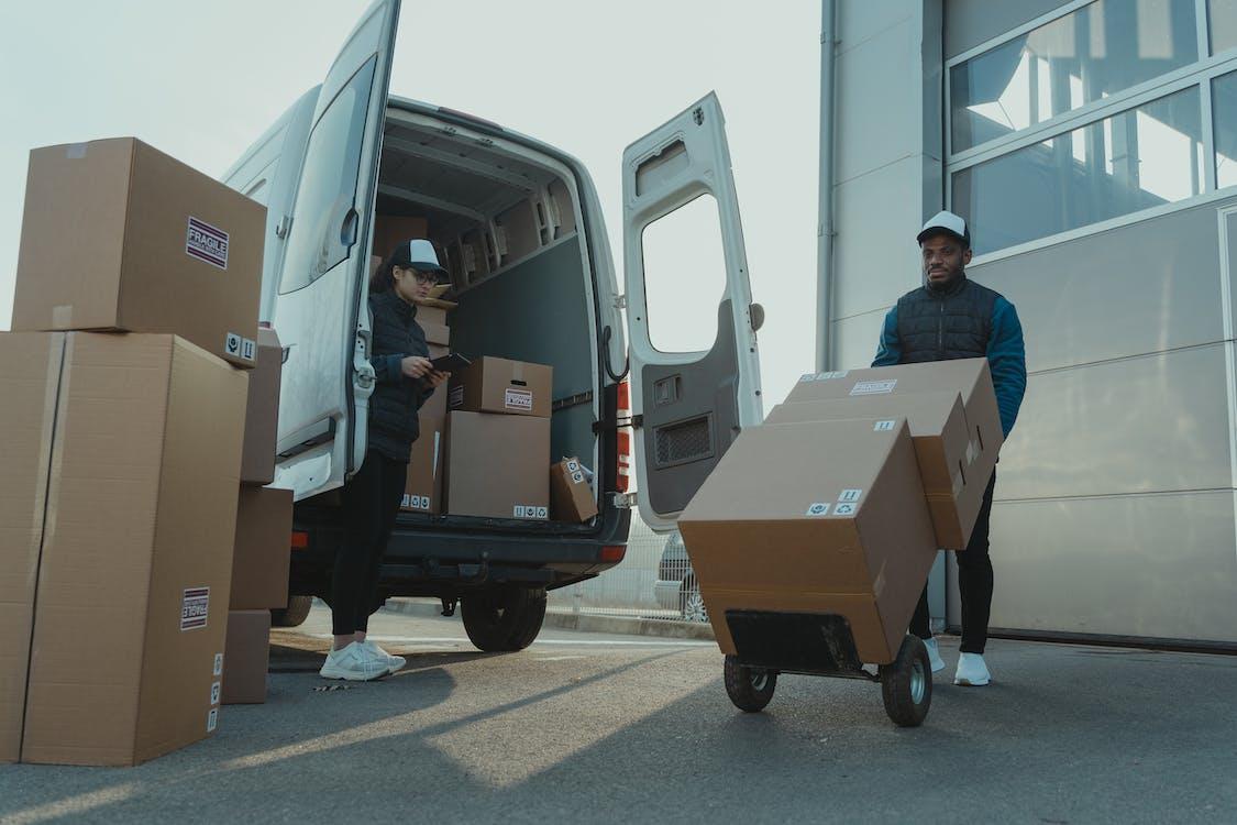 Man in Black Jacket and Black Pants Standing Beside Brown Cardboard Box