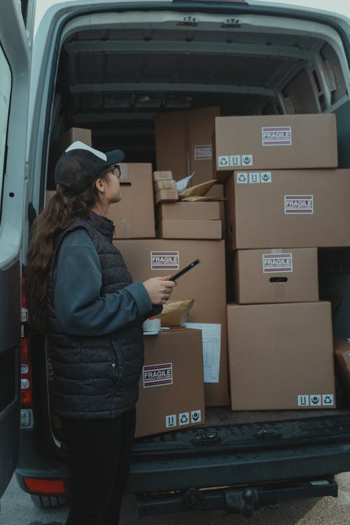 ]A Woman Checking a Van Delivery Contents