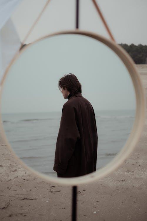 Stylish man model standing on sandy coast near sea
