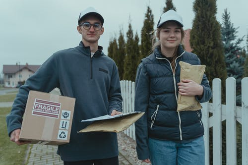 A Man and a Woman Holding Delivery Packages