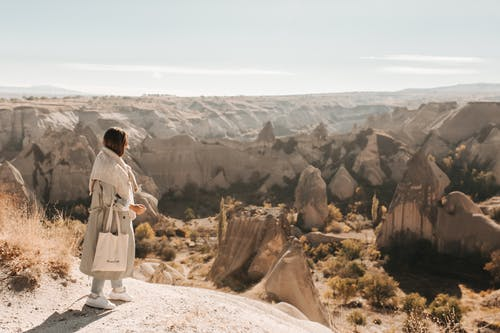Full body side view of unrecognizable female traveler with bag standing on edge of stony hill above mountainous terrain in canyon