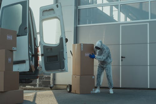 A Person Wearing Personal Protective Equipment in Handling Packages