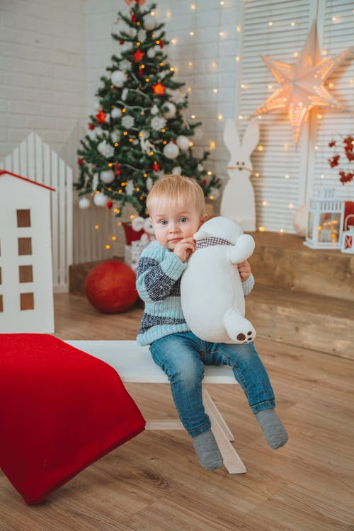 Adorable toddler in warm sweater sitting on bench with toy against Christmas tree and various glowing garlands