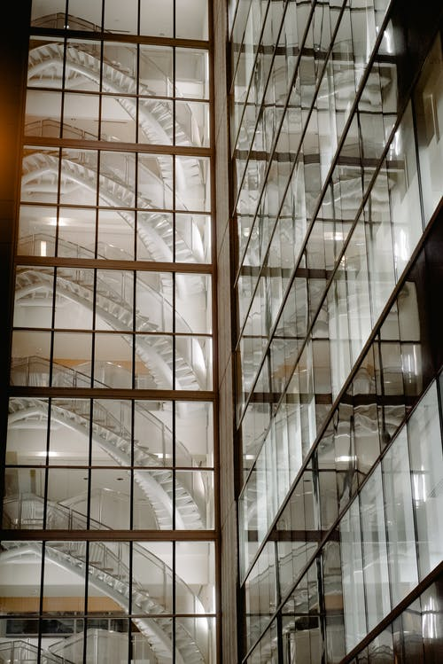 Spiral staircases and bright lighting behind glass of contemporary multistory house with transparent windows located in street at night time