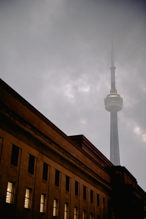 Top of old residential building located near tall tower against foggy cloudy sky on gloomy weather on street in city